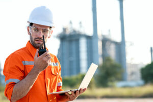 Male Maintenance engineer working on fuel and power generation plant, using laptop and communicate by walkies talkies outdoors.