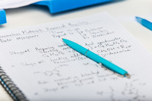 Notepad with scientific research report and blue pen on laboratory table with selective focus effect